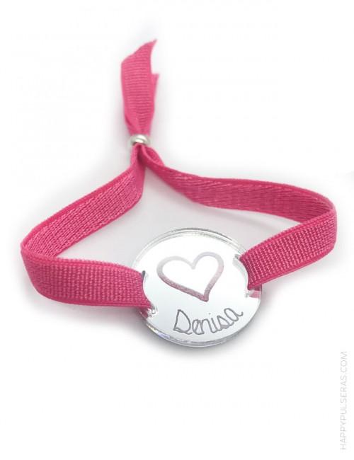 Pulsera ajustable para grabar tu nombre sobre el acrílico redondo con elástico en color rosa fresa.