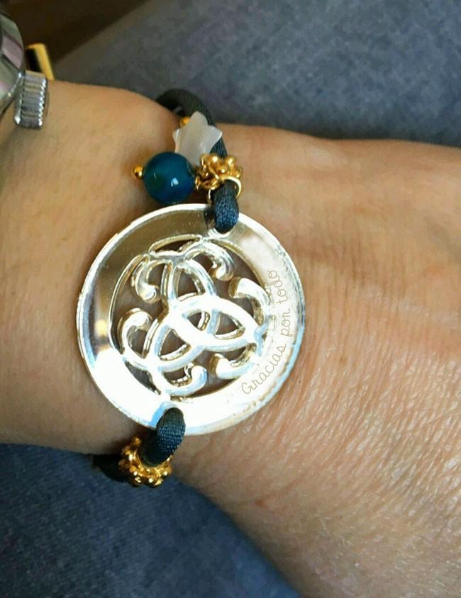 pulsera con adorno redondo tribal en acrílico color oro efecto espejo con cordón elástico seda