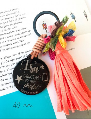 Llavero pompón de colores con medalla de titanio negro grabada con una dedicatoria. Happypulseras.