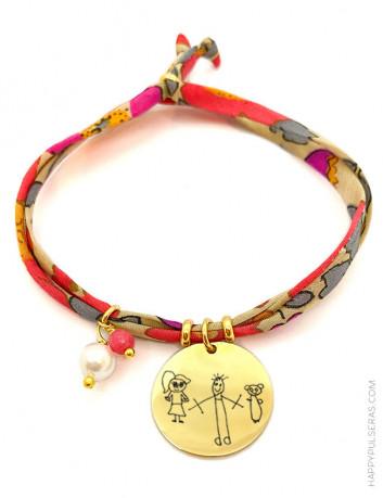 Pulsera con medalla de acero dorado grabada con el dibujo de tu peque y cordón de tela de flores en tonos rojos de flores