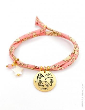 Pulsera con medalla de acero dorado grabada con el dibujo de tu peque y cordón de tela de flores en tonos rosa claro