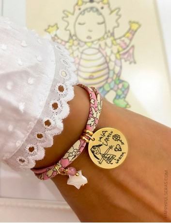 Pulsera tela de flores rosa pastel con medalla dorada grabada a ambas caras, con dedicatoria y dibujo de tu hijo.